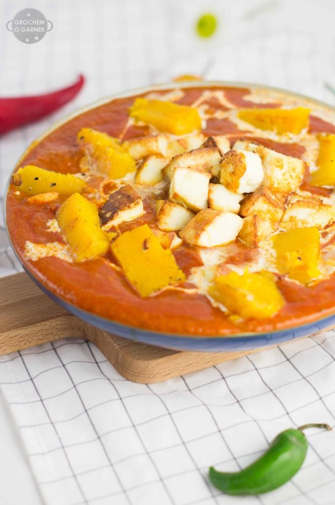 Czy wiesz, że koncentrat pomidorowy jest  świetnym źródłem likopenu, który jest silnym przeciwutleniaczem (antyoksydantem). Pomaga naszemu ciału zwalczać wolne rodniki i przez to obronić się przed rakiem. Za to pomidory z puszki mają w sobie ogromne pokłady witaminy A, potasu oraz magnezu. I chociaż trudno w to uwierzyć, to warto spożywać przetwory pomidorowe częściej niż świeże pomidory. Zarówno koncentrat pomiodorowy jak i puszki z pomidorami to jest to, co zawsze mam w swojej spiżarni. Można z nich wyczarować przepyszny sos w zaledwie kilka minut i tylko od nas zależy jaki nadamy mu charakter. Akurat dzisiaj miałam ochotę na coś bardziej azjatyckiego, jednak z dyniową, jeszcze jesienną nutą.   Skład (2-4 porcje): 1 puszka krojonych pomidorów, 1 czerwona cebula, 2 ząbki czosnku, 2cm korzeń imbiru, 2 łyżeczki czerwonej pasty curry, 2-3 łyżki miodu lub syropu klonowego, 4 łyżki koncentratu pomidorowego, 1/2 puszki mleka kokosowego + trochę do ozdobienia, sok z 1 limonki, olej kokosowy lub masło klarowane do smażenia, sól do smaku. 1/2 upieczonej dyni piżmowej*, ser paneer (zrób go w domu - tutaj przepis!) do podania polecam ryż basmati. *Dynię przekroić na pół i przekrojoną stroną do dołu piec w 180st przez około 40 min. Następnie wydrążyć nasiona, obrać ze skórki i pokroić w kostkę. Do tego przepisu potrzebujemy 1/2 dyni (po inne przepisy z dynią wejdź tutaj).  Cebule, czosnek i imbir drobno posiekać i lekko podsmażyć. Następnie posolić i dodać miód oraz pastę curry, całość smażyć do zezłocenia. Do smażących się przypraw dodać koncentrat pomidorowy, wymieszać chwilę podsmażać. Następnie wlać puszkę krojonych pomidorów. Pomidory odparowywać, aż będą miały gładką konsystencje, możliwe, że będzie trzeba dodać trochę wody, żeby pomidory się rozpadły. Pod koniec gotowania dodać mleko kokosowe i sok z limonki. Curry podawać z podsmażonym serem panner lub tofu, upieczoną dynią pokrojoną w kostkę oraz ryżem. Szybki obiad wegetariański - curry-z-dynią